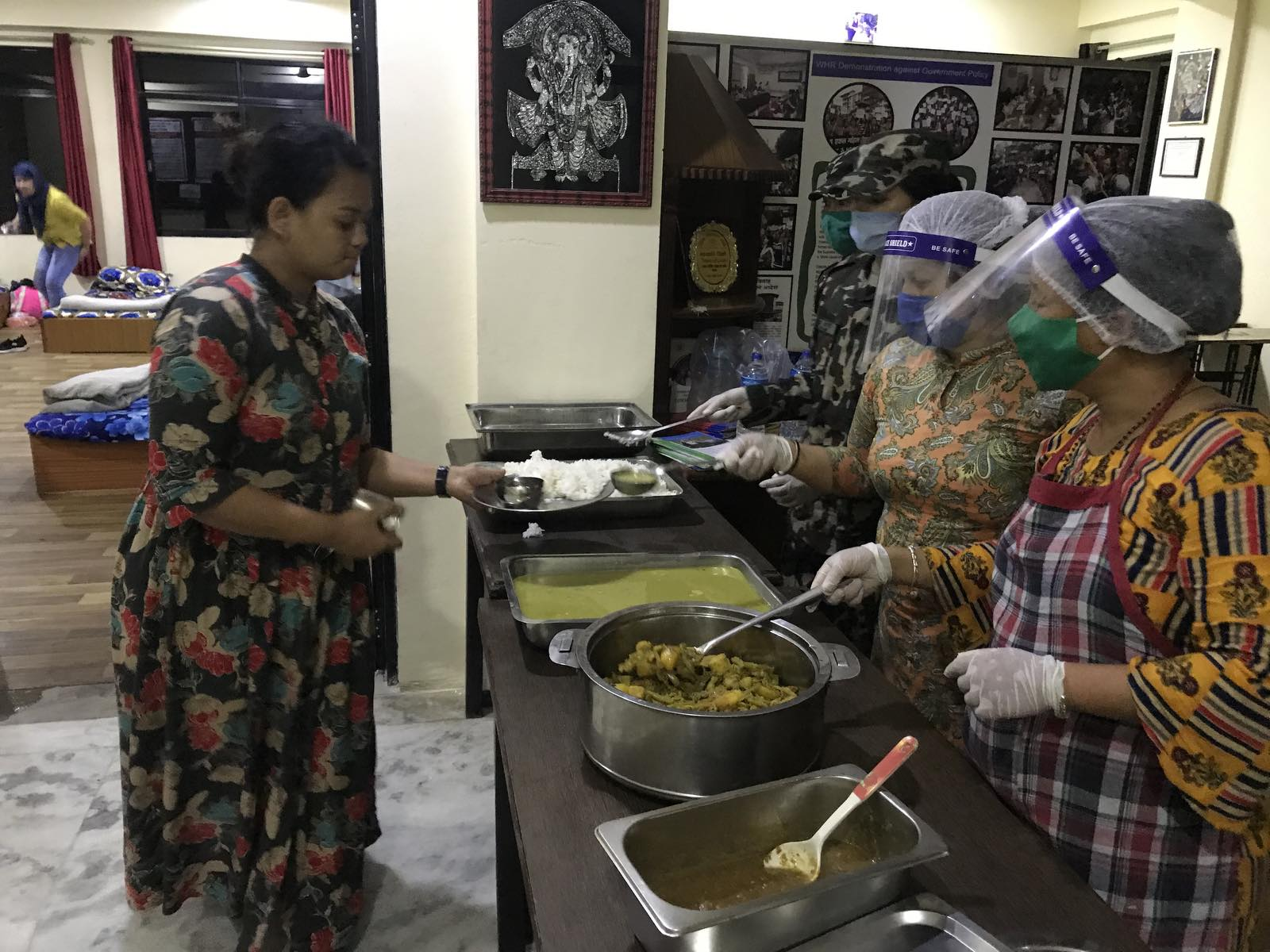 Community-kitchen-staffs-using-necessary-safety-gears-while-serving-food